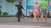 pomáhá : NHA TRANG. VIETNAM - CIRCA JAN 2016: Traffic officer assists tourists in crossing a busy street in Nha Trang. UltraHD 4k footage