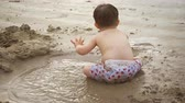 outing : Adorable and playful toddler. throwing fistfulls of wet sand and sitting in a puddle at a popular public beach. 4k footage