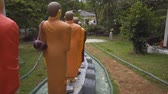 ganga : MADUGANGA LAKE . SRI LANKA - DEC 2016: Painted statues of venerated monks in a long line. outside a Buddhist temple in Madu Ganga. Ultra HD 4k video