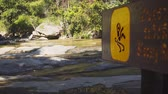 deslizamento : Safety sign warns of a slipping hazard on the bank of a mountain stream. near Mae Ya Waterfall. 4k stock footage