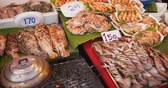 sortido : Variety of grilled seafoods. including squid. tilapia. crabs and prawns. displayed for sale at an outdoor public market in Asia. DCI 4k video Stock Footage