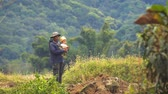 supervising : CHIANG MAI. THAILAND - JAN 2018: Local man stands. overseeing farm work while holding his young son in his arms.
