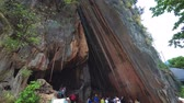 плиты : PHANG-NGA. THAILAND - APR 2018: Tourist viewing an enormous fractured slab of limestone. split from a natural formation on Ko Tapu. Стоковые видеозаписи