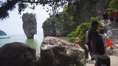 provincie : PHANG-NGA. THAILAND - APR 2018: Tourists Photographing a Dramatic Limestone Formation on James Bond Island in southern Thailand. Ultra HD stock footage
