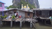 cami : Gold-domed mosque and dramatic limstone formation presiding over these houses on stilts at the remote Panyee Island. in Thailand. Ultra HD stock footage Stok Video