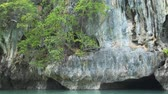 sea caves : Caves and hollows. cut by natural processes in this giant limestone formation off the coast of Phang Nga Province. in Thailand. FullHD footage Stock Footage