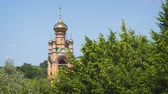 spirituality : Tower with arches and golden domes of Sviato-Pokrovskyi Golosiiv Monastery. stands above the trees in Kiev. Ukraine. 4k footage