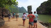 tapu : PHANG-NGA. THAILAND - APR 2018: Visitors in front of a dramatic rock formation on James Bond Island. 4k stock footage