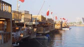denteado : DOHA. STATE OF QATAR - MAY 2018: Qatari National Flags Flying from wooden boats in Doha harbor.
