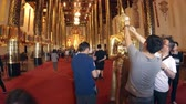 coluna : CHIANG MAI. THAILAND JAN 2018: Worshippers Applying Gold Leaf to Buddha Statue as an Offering. Video UltraHD 4k Vídeos