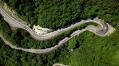 Aerial fly under curved winding road trough the mountains