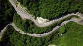 dobrar : Aerial fly over a curved winding road trough the mountains with cars and truck