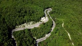 Aerial view of a curved winding road trough the mountains with cars and truck