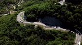 enrolamento : Aerial view of a curved winding road trough the mountains with cars and POV truck.