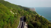 Aerial view of a curved winding road trough the mountains to Sochi, Russia near Black Sea