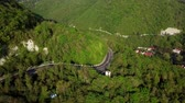 Aerial view of a curved winding road trough the mountains with green trees Stok Video