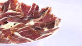 serrano : view of pile of typical spanish iberico ham sliced on dish rotating spinning on white background