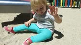 slither : two years old blonde lovely caucasian laughing happy baby grey shirt green trousers with mother slithering on slide toboggan in playground outdoor park Stock Footage