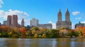 américa central : Boating in New York City Central Park in Autumn with skyscrapers apartment and lake Stock Footage