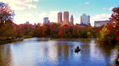 New York City Central Park in Autumn with skyscrapers apartment boat and lake