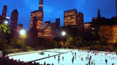 Ice Rink panorama in Central Park in winter with people skate in Midtown New York City