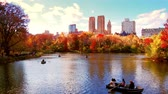 new day : New York City Central Park in Autumn with skyscrapers apartment boat and lake
