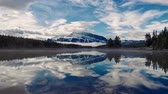 tomada : Two Jack Lake timelapse cloudscape and snow mountain reflection in Banff National Park, Canada.