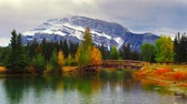 banff : Wood bridge snow mountain and autumn foliage over lake with ripple in Banff National Park, Canada. Stock Footage