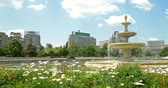 piata : BUCHAREST, ROMANIA - JUNE 15, 2016: Union Square Fountain And House Of The People Or Parliament Palace (Casa Poporului) View From Union Boulevard (Bulevardul Unirii) In Downtown Bucharest.