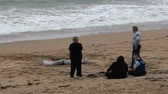 assassinato : CABLE BAY, NZL - MAR 02 2015:Police officers investigate eyewitness that found body washes ashore.According to International Rewards Center about 607 people go missing every day around the world.