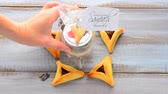 judaísmo : Woman hand placing a Purim basket (Mishloach manot) in side a Star of David made out of Purim Cookies - Hamentashen (Ozen Haman) for Purim Jewish Holiday. Copy space Vídeos