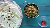 naan : Flat lay view of Indian woman hands serve Alu Methi with Naan flatbread and fresh chilli.Food background of West, Central and South Asia cuisines. copy space Stock Footage