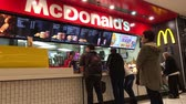 cena urbana : Customers buy fast food in Mcdonalds shop. McDonalds is the worlds largest restaurant chain by revenue, serving over 69 million customers daily in over 100 countries.