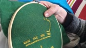 borduur : Woman embroidery at home. Embroidery is the craft of decorating fabric or other materials using a needle to apply thread or yarn. Close-up details. Stockvideo