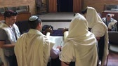 kaydırma : Jewish men reading and praying from a Torah scroll. Reading the Torah is one of the bases for Jewish life. Stok Video