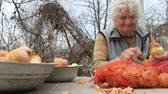 peeling onion : An old woman with gray hair picks up onions before cooking in the kitchen, organic vegetables, her own crop, selective focus Stock Footage