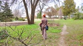 протектор : Rear view of a young adult woman with a short red haircut walks through the botanical garden in spring. Стоковые видеозаписи