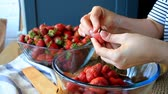 投げる : Close up of female hands peel fresh large strawberries for later use