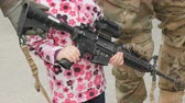 абориген : Girl with pink jacket holds a machine gun and standing next to the soldiers.