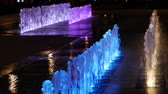 A close up shot of a fountain water feature clear water line and jets with changing colour LED light, evening.