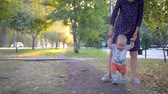 first : The child makes the first steps, mother help him. Autumn park.