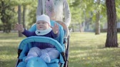 pram : Mom rolls toddler in a stroller. Baby waving his arms, smiling and playing. Outdoor.