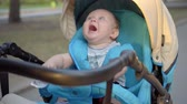 pram : The kid rides in a carriage and waving hands of the packages with baby food in their hands. Stock Footage