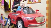 kâkül : Little boy cuts the barber. He sits in a chair that looks like a car.