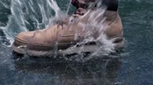 Close-up View of Man in Boots Step on a Puddle and Create a Splash in Slow Motion 影像素材