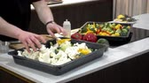 chef quipe : 4K view of chef mixes vegetables for cooking. Broccoli, cauliflower and pepper marinated in a tray on the table.