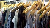 womens : Womens clothes hanging on the wooden hangers on the rack in the store. HD video