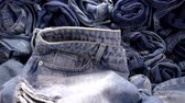 spodnie : Slow Motion of falling jeans on a pile of denim trousers. Wideo