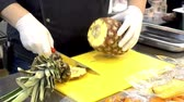 eat : The cook cuts pineapple in the kitchen. Preparation of ingredients for cooking in a restaurant.