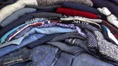 brim : Pile of colorful clothes as a background. Jeans, T-shirts and Sweaters are piled up in a heap. HD video